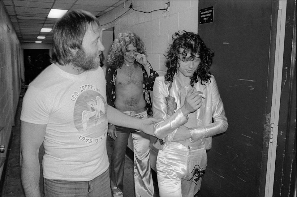 <p>Jimmy Page (fore, right) and Robert Plant (center, rear) as they walk backstage at Madison Square Garden, New York, New York, June 10, 1977.</p>
