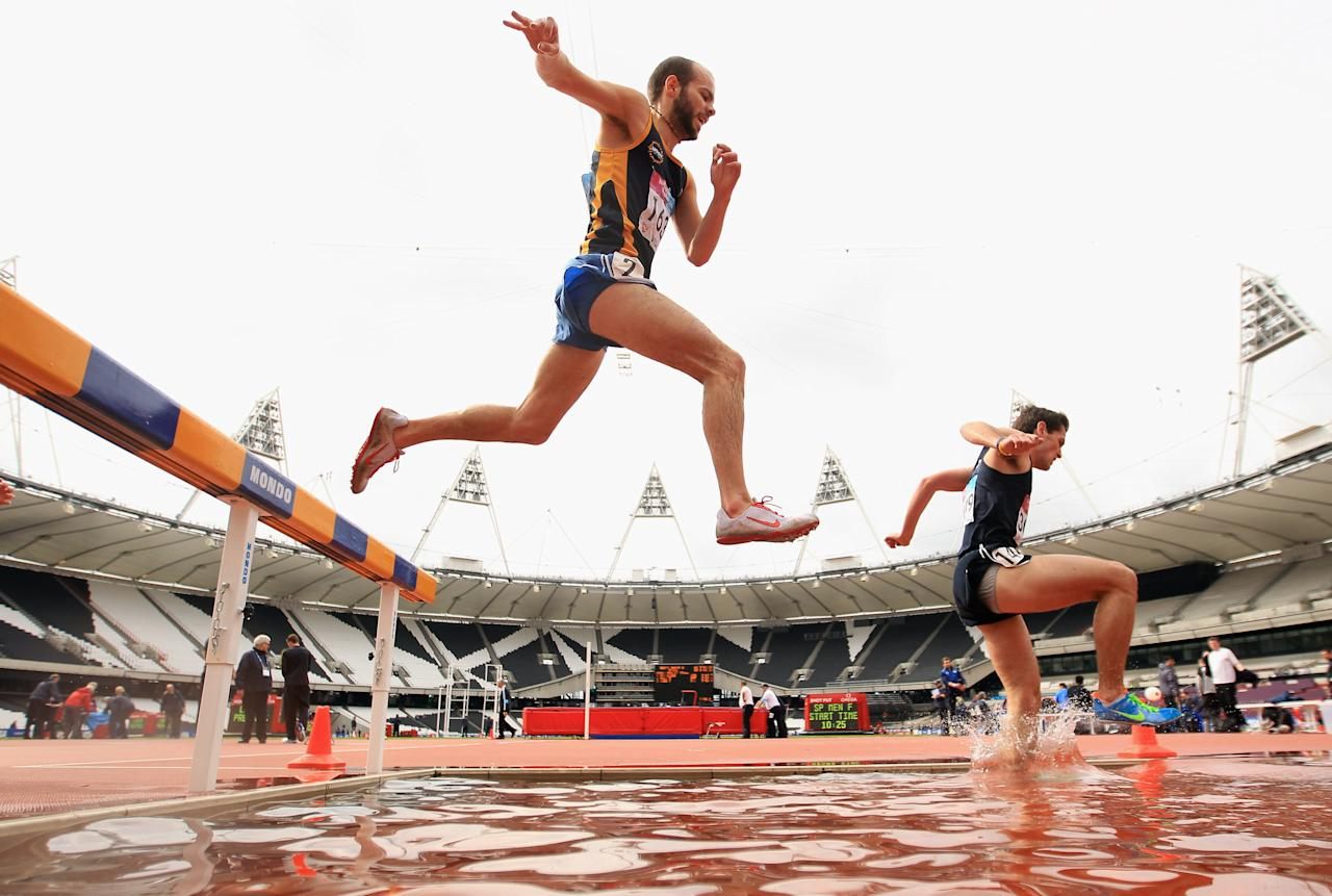 LONDON, ENGLAND - MAY 07:  Competitors run through the water splash in the Men's 5000m steeple chase during day four of the BUCS VISA Athletics Championships 2012 - LOCOG Test Event for London 2012 at Olympic Stadium on May 7, 2012 in London, England.  (Photo by Bryn Lennon/Getty Images)