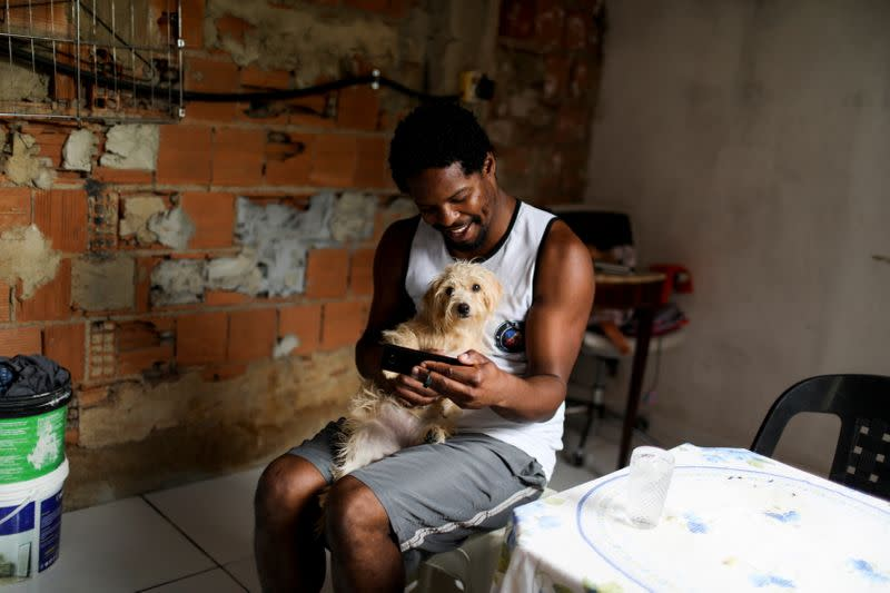 The Wider Image: Scholar by day, street-sweeper by night, one Black man navigates Rio's racial divide