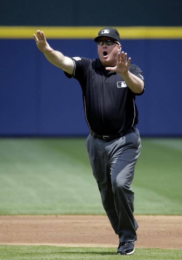 Umpire Bill Miller tells Cincinnati Reds manager Bryan Price not to come on the field after an instant replay decision was made in favor of the Atlanta Braves as Price ignored Miller's warning leading to his ejection in the first inning of a baseball game, Sunday, April 27, 2014, in Atlanta. (AP Photo/David Goldman)