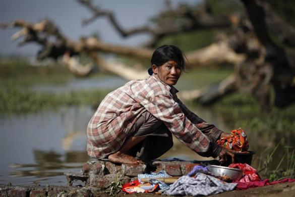 A woman washes clothes at a river in the outskirts of capital Naypyitaw, January 24, 2012.