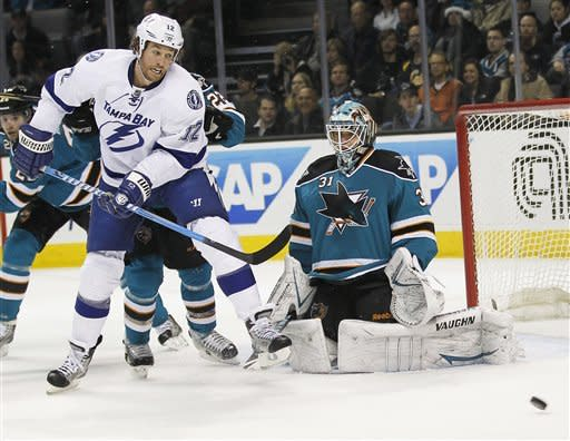 San Jose Sharks goalie Antti Niemi, of Finland, right, blocks a shot attempt Tampa Bay Lightning left wing Ryan Malone (12) during the first period of an NHL hockey game in San Jose, Calif., Wednesday, Dec. 21, 2011. (AP Photo/Tony Avelar)