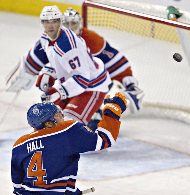 New York Rangers' Benoit Pouliot (67) and Edmonton Oilers goalie Jason LaBarbera (1) watch as Edmonton's Taylor Hall (4) bats the puck out of the air during the second period of an NHL hockey preseason game, Tuesday, Sept. 24, 2013, in Edmonton, Alberta. (AP Photo/The Canadian Press, Jason Franson)