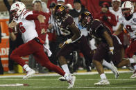 Nebraska quarterback Noah Vedral, left, runs with the ball in front of Minnesota defensive backs Jordan Howden (23) Antoine Winfield Jr. (11) during an NCAA college football game Saturday, Oct. 12, 2019, in Minneapolis. (AP Photo/Stacy Bengs)
