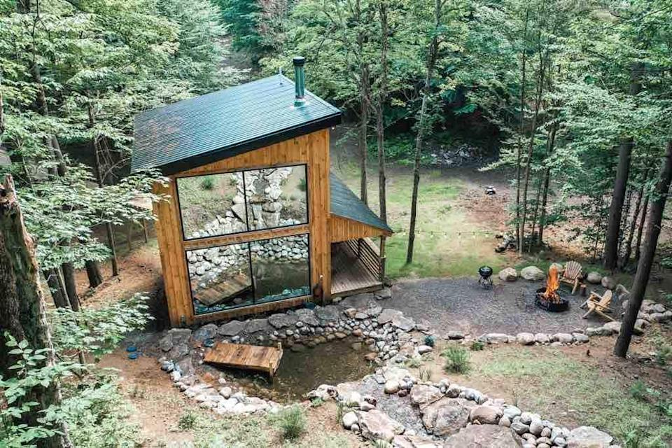 """Where better to have a view of autumn's colors than elevated in a treehouse? This modern log cabin, built 14 feet off the ground, has floor-to-ceiling picture windows that offer views not only of the surrounding forest, but of the 50-foot waterfall in the home's backyard. Best for families, there are two bedrooms here, one with a king bed and the other with built-in bunk beds—though you have to walk through the master to reach the bunk room. There's a 500-square-foot wraparound front porch, fire pit area with a grill, and access to a pond on property as well. While not as secluded as other cabins on this list (there is <a href=""""https://cna.st/affiliate-link/MQqxxtNLYnQ8oFkSN7SzyJEpCNKRmWDLCDx3k95XqhHVQi5qv6vdQfJyUSAhK3aMXhqXW8rADvMbiFYfMrk2YZ9eWH?cid=5f6cb36edf42258e52b728c4"""" rel=""""nofollow noopener"""" target=""""_blank"""" data-ylk=""""slk:another Airbnb"""" class=""""link rapid-noclick-resp"""">another Airbnb</a> on the hosts' property), previous guests tout that it feels completely private. $489, Airbnb (Starting Price). <a href=""""https://www.airbnb.com/rooms/28436865"""" rel=""""nofollow noopener"""" target=""""_blank"""" data-ylk=""""slk:Get it now!"""" class=""""link rapid-noclick-resp"""">Get it now!</a>"""