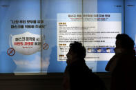 """People wearing face masks walk near a screen displaying precautions against the coronavirus in Seoul, South Korea, Sunday, Dec. 27, 2020. A banner reads: """"People who do not wear masks in public will face a 100,000 won (US$90) fine."""" (AP Photo/Lee Jin-man)"""