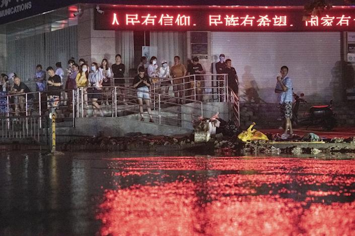 People gather outside a building under a neon sign with Chinese characters