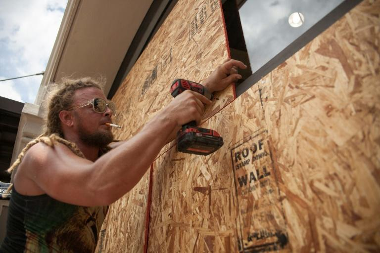 Matt Harrington boards up a Vans shoe store near the French Quarter in New Orleans as tropical storm Barry approaches (AFP Photo/Seth HERALD)