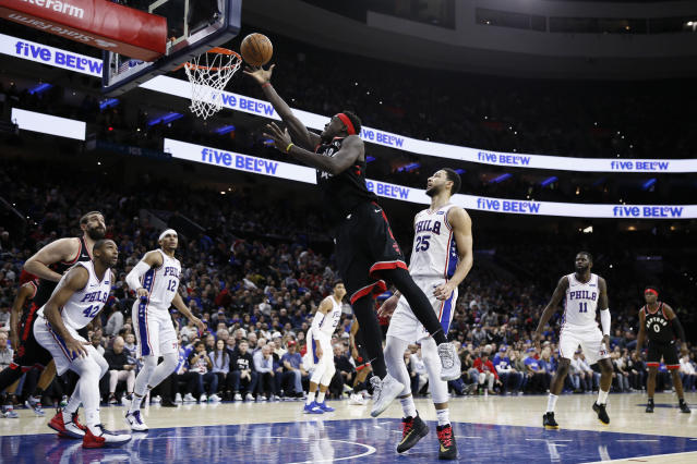 Toronto Raptors' Pascal Siakam, center, left, goes up for a shot past Philadelphia 76ers' Ben Simmons, center right, during the first half of an NBA basketball game, Sunday, Dec. 8, 2019, in Philadelphia. (AP Photo/Matt Slocum)