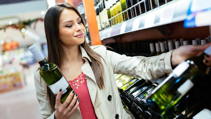 Woman deciding what wine to buy and shopping in supermarket.