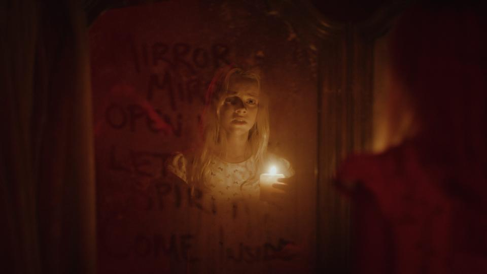 """Young Claire (Elizabeth Birkner) accidentally unleashes a demon from a haunted mirror in the horror film """"Behind You."""""""