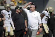 FILE - In this Sunday, Sept. 12, 2021, file photo, New Orleans Saints head coach Sean Payton, center, watches players warm up before an NFL football game against the Green Bay Packers in Jacksonville, Fla. Six unidentified members of the Saints coaching staff, a player and a nutritionist have tested positive for COVID-19, two people familiar with the situation said, Tuesday, Sept. 14, 2021. The people spoke with The Associated Press on Tuesday on condition of anonymity because the team and NFL had not made a public statement about the matter. The names of those who tested positive were not expected to be released in the short term because of federal medical privacy laws. (AP Photo/Phelan M. Ebenhack, File)