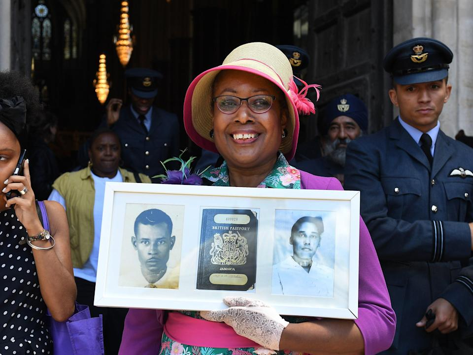 <p>Andria Marsh holds up photographs of her parents and her original British passport after a service at Westminster Abbey in celebration of 70 years since the arrival of Empire Windrush, 22 June 2018</p> (EPA-EFE)