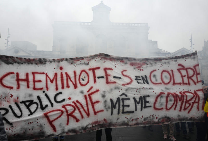 """Rail workers demonstrate during a mass strike in Lille, northen France, Thursday, Dec. 5, 2019. Workers across the public sector fear President Emmanuel Macron's reform will force them to work longer and shrink their pensions. Banner reads: """"Angry railway worker, private and public same fight"""". (AP Photo/Michel Spingler)"""