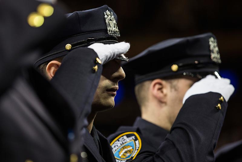 New York Police Department recruits salute during the NYPD graduation ceremony at Madison Square Garden in New York City on December 29, 2015. (Andrew Burton via Getty Images)