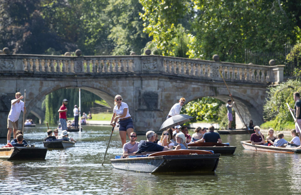 People punt along the River Cam in Cambridge, England, Sunday Aug. 25, 2019, as the hot weather continues throughout the weekend. (Joe Giddens/PA via AP)