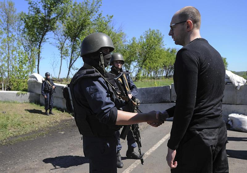 FILE - In this May 7, 2014 file photo, Ukrainian Prime Minister Arseniy Yatsenyuk, right, shakes hands with Ukrainian soldiers at a block post on the road at Slovyansk, Ukraine. Yatsenyuk's interim government is seeking to carry out sweeping reforms to break from a culture of self-interest, cynicism and corruption that left the country on the verge of bankruptcy. (AP Photo/Andrew Kravchenko, Pool, File)