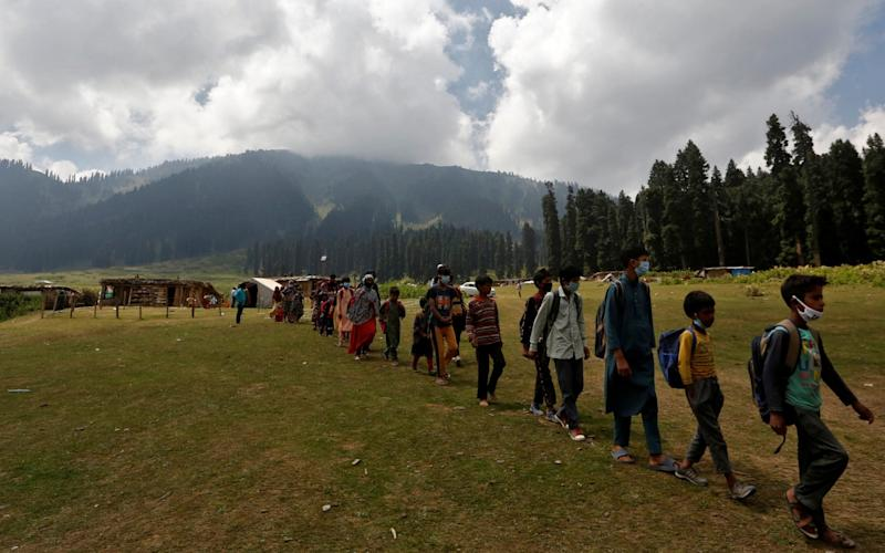 Children, who miss their online classes due to lack of internet, walk in a line as they leave after attending their open-air classes after schools were closed in central Kashmir's Budgam district - Reuters