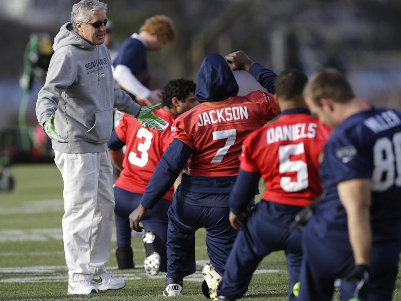 Seattle Seahawks coach Pete Carroll, left, talks with backup quarterback Tarvaris Jackson (7) during stretching drills before NFL football practice, Friday, Jan. 3, 2014, in Renton, Wash. Seattle plays at home in a playoff game on Jan. 11. (AP Photo/Ted S. Warren)