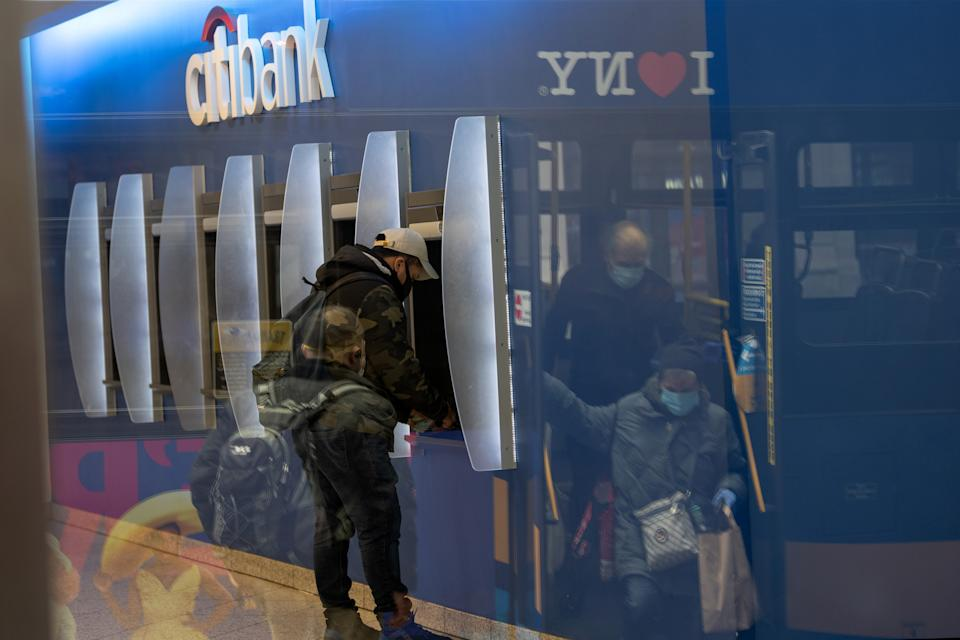 NEW YORK, NY - APRIL 17: A man wearing a protective mask uses an ATM while people wearing gloves and a mask can be seen getting off a bus in the reflection of the bank's window amid the coronavirus pandemic on April 17, 2020 in New York City, United States. COVID-19 has spread to most countries around the world, claiming over 160,000 lives with over 2.3 million cases. (Photo by Alexi Rosenfeld/Getty Images)