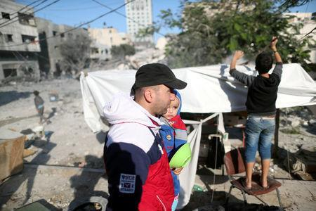 A Palestinian man carries his son at the site of an Israeli air strike on a building, in Gaza City November 13, 2018. REUTERS/Suhaib Salem