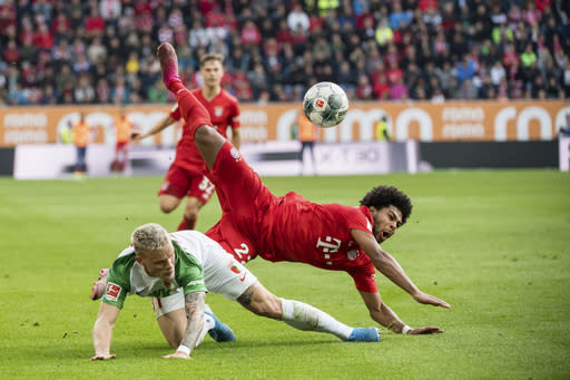 Augsburg's Philipp Max and Munich's Serge Gnabry challenge for the ball during a German Bundesliga soccer match between FC Augsburg and Bayern Munich in Augsburg, Germany, Saturday, Oct.19, 2019. (Matthias Balk/dpa via AP)