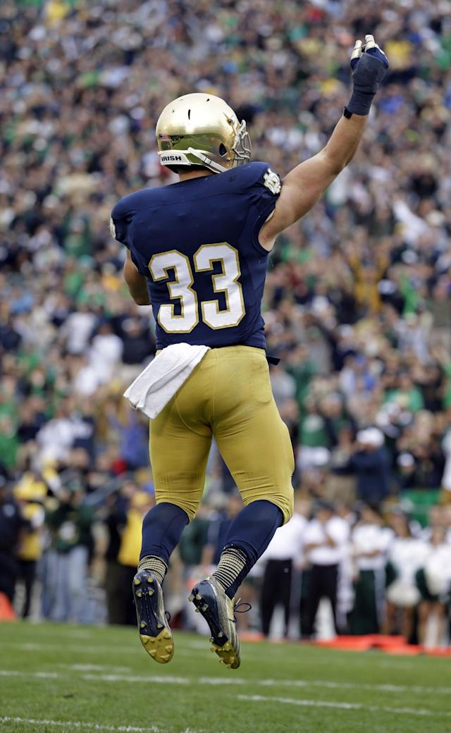 Notre Dame running back Cam McDaniel celebrates a touchdown against Michigan State during the second half of an NCAA college football game in South Bend, Ind., Saturday, Sept. 21, 2013. Notre Dame won 17-13. (AP Photo/Michael Conroy)