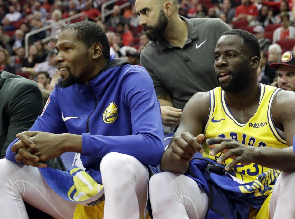 Kevin Durant and Draymond Green sit together on the bench during the first half Thursday night during a loss to the Rockets. (AP)