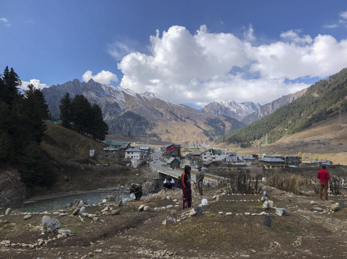 Relatives of suspected rebels killed by government forces visit a graveyard in Sonamarg, a remote mountainous resort in Indian controlled Kashmir, Nov.3, 2020. The picturesque tourist spot where a small hill meant for the bodies of rebels started small in April has since nearly filled up. Indian authorities in a new controversial policy in 2020 started to consign blood-soaked bodies of scores of Kashmiri rebels to unmarked graves, denying the mourning families a proper funeral and a burial at their own ancestral home graveyards. (AP Photo/Aijaz Hussain)