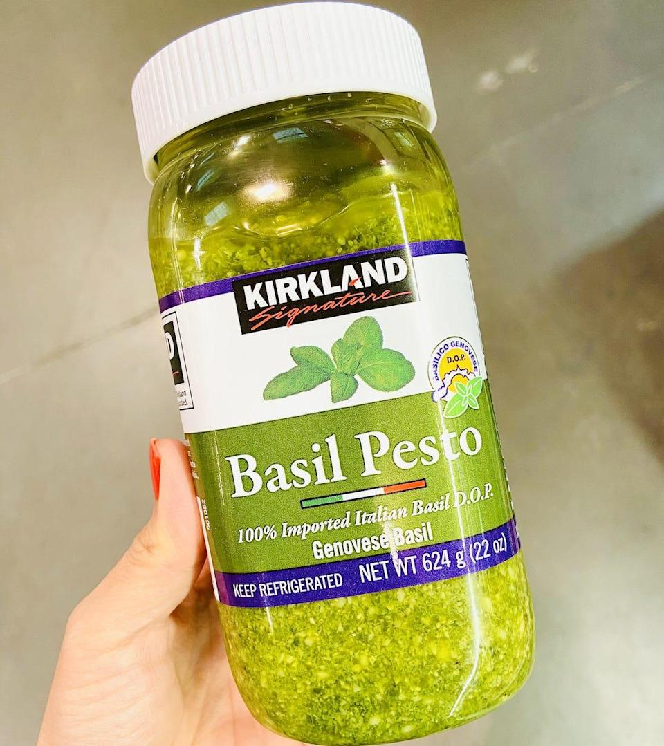 Hand holding a jar of bright green pesto from costco