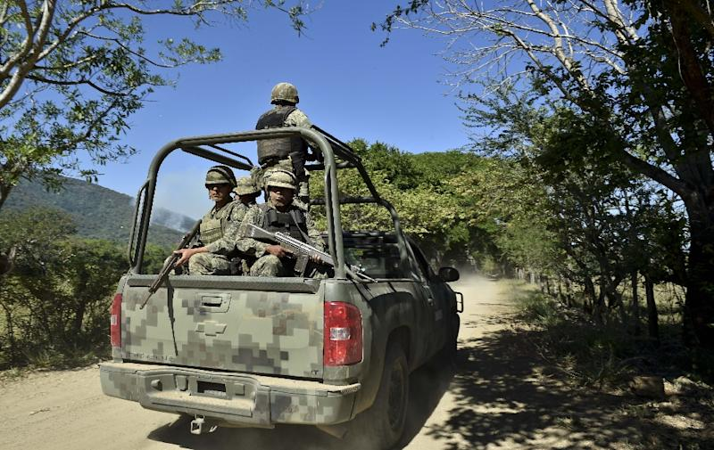 Soldiers of the 88th infantry brigade patrol the area around the site where a military helicopter was shot down two days ago, in Villa Vieja community, Jalisco State, Mexico, on May 3, 2015 (AFP Photo/Yuri Cortez)