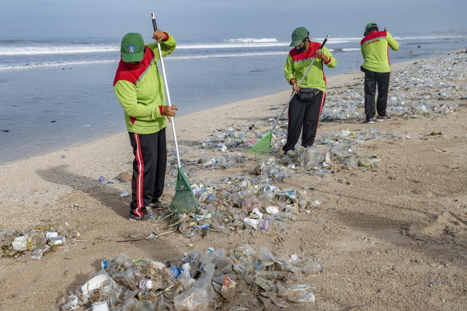 Three workers with rakes clean up mounds of plastic and rubbish that have washed up on a Bali beach.