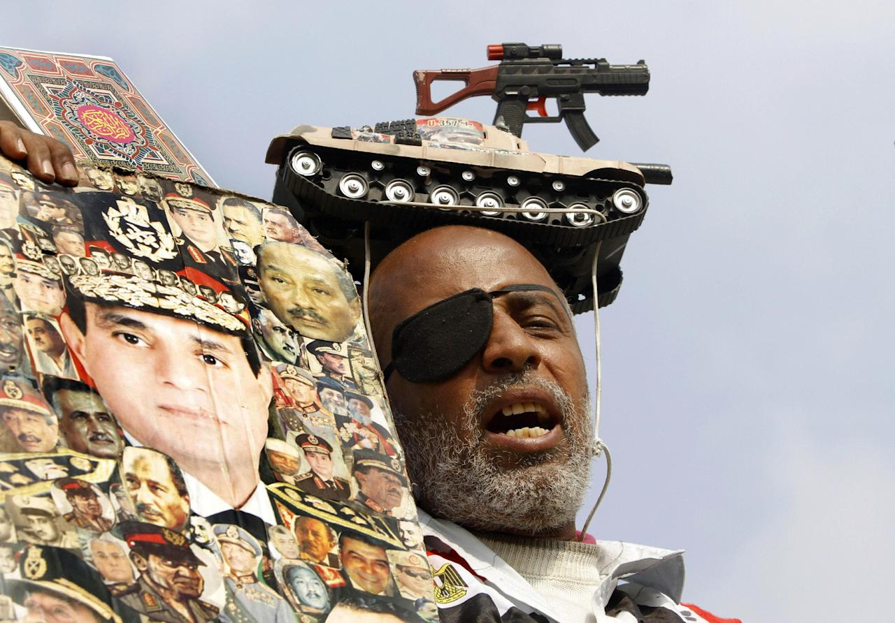 An Egyptian wears a toy weapon and tank on his head as he holds a poster showing Egyptian Defense Minister Gen. Abdel-Fattah el-Sissi surrounded by pictures of late Presidents Anwar Sadat and Gamal Abdel-Nasser during a celebration marking Sissi's birthday in Tahrir Square, in Cairo, Egypt, Tuesday, Nov. 19, 2013. Egypt's revolutionary groups are marking Tuesday the second anniversary of some of the fiercest confrontations between Egyptian protesters and security forces in Mohammed Mahmoud street where scores had been killed. Rallies are also expected later in the day amid fears of more unrest and violence. (AP Photo/Amr Nabil)
