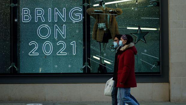 """Two people, wearing blue disposable masks, walk past a store with a neon window sign that says """"bring on 2021"""" in large capital letters."""