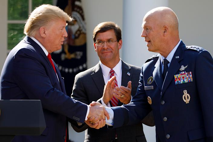 "President Donald Trump, joined by Secretary of Defense Mark Esper, shakes hands with Gen. John ""Jay"" Raymond on Aug. 29, 2019."