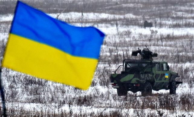Ukraine's flag flies in front of a new armored car, near the city of Goncharivsk on January 23, 2015 (AFP Photo/Sergei Supinsky)