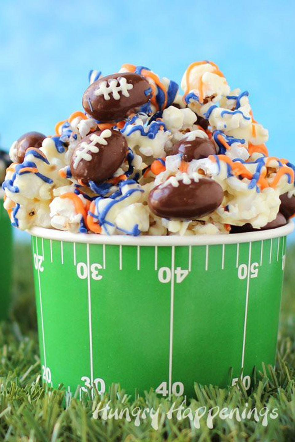 """<p>Customize this white chocolate popcorn with your favorite team's colors.</p><p><strong>Get the recipe at <a href=""""http://hungryhappenings.com/super-bowl-popcorn-with-chocolate-almond-footballs.html/"""" rel=""""nofollow noopener"""" target=""""_blank"""" data-ylk=""""slk:Hungry Happenings"""" class=""""link rapid-noclick-resp"""">Hungry Happenings</a>.</strong></p>"""