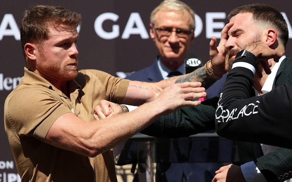 Canelo Alvarez slaps Caleb Plant during a face-off before a press conference - Getty Images