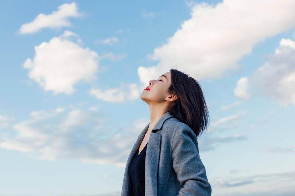 An image of a woman looking up to the clouds in the sky