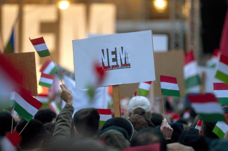 """Participants wave Hungarian national flags and hold a placard reading """"No"""", as thousands of people attend a protest called Mass Demonstration Against Nazism in front of the Parliament building, unseen, in Budapest, Hungary, Sunday, Dec. 2, 2012. The protest has been provoked by MP of Jobbik party Marton Gyongyosi who demanded a list on Jewish Hungarians who are members of the Parliament or the government. (AP Photo/MTI, Janos Marjai)"""