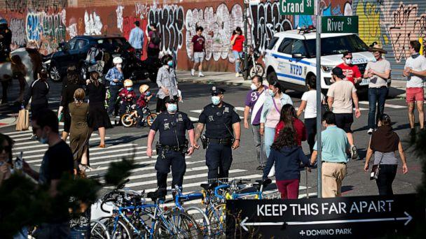 PHOTO: Police officers patrol near a social distancing sign in front of Domino Park during the coronavirus pandemic in the Brooklyn borough of New York City, May 3, 2020. (Michael Nagle/Redux)