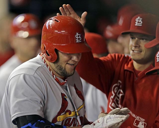 St. Louis Cardinals' Matt Adams is congratulated in the dugout after hitting a two-run home run against the Milwaukee Brewers in the first inning of a baseball game Saturday, Sept. 21, 2013, in Milwaukee. (AP Photo/Jeffrey Phelps)