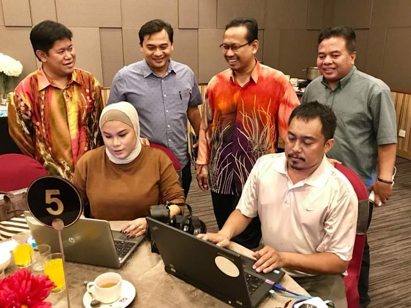 Johor Speaker Suhaizan Kaiat (standing, third left) and Johor Media Club president Mohamad Fauzi Ishak (standing, second left) being briefed on how reporters and media practitioners upload their story for online news in Johor Baru today. — Picture by Ben Tan