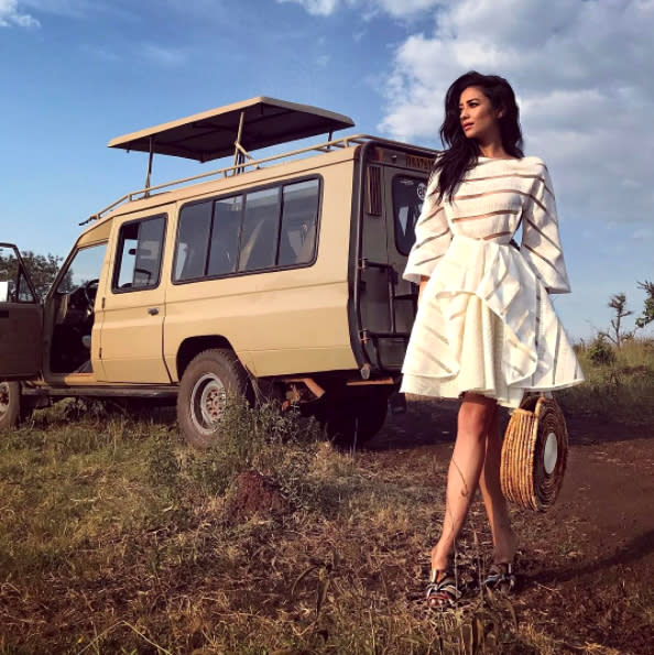 Shay Mitchell in a white dress and heels on location next to a safari vehicle.