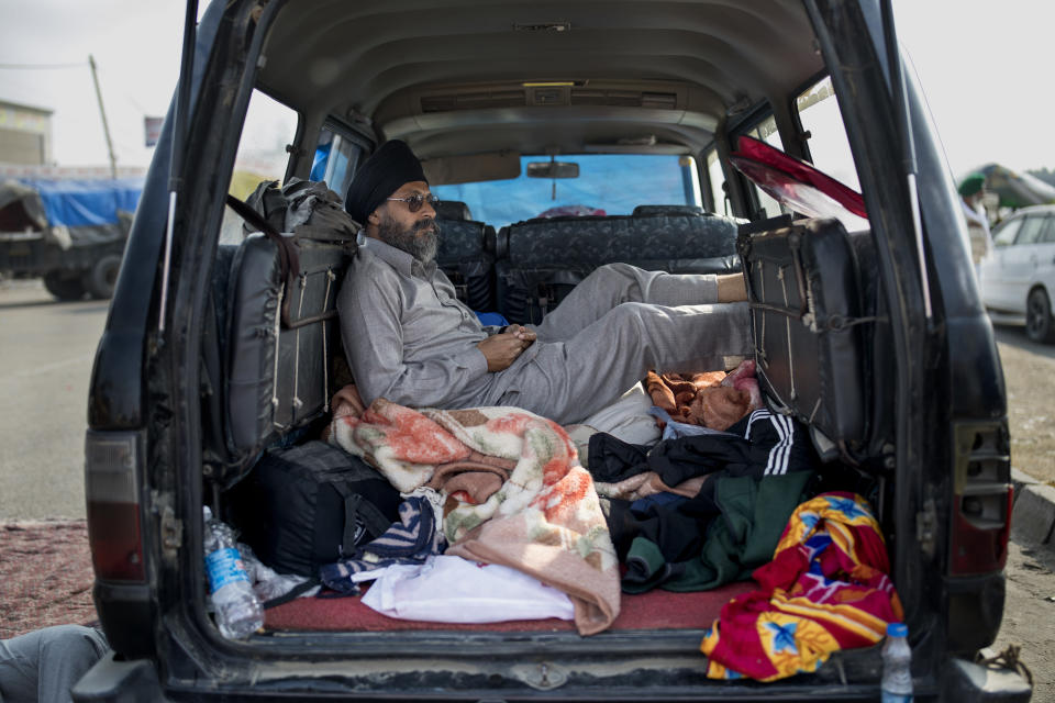 Savek Singh, 48, rests inside his vehicle parked on a highway as he joins a farmers protest, at the Delhi-Haryana state border, India, Tuesday, Dec. 1, 2020. The farmers are protesting new laws they say will result in their exploitation by corporations, eventually rendering them landless. Prime Minister Narendra Modi's government, rattled by the growing rebellion, insists the reforms will benefit them. But the farmers aren't yielding. (AP Photo/Altaf Qadri)