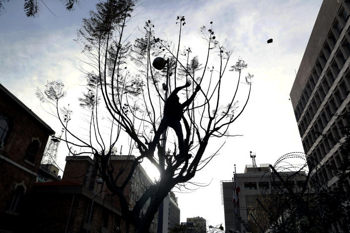A protester on a tree throws stones towards the central bank building, during a protest in Beirut, Lebanon, Saturday, March. 13, 2021. Riot police fired tear gas to disperse scores of people who protested near parliament building in central Beirut Saturday amid deteriorating economic and financial conditions and as the local currency hit new low levels (AP Photo/Bilal Hussein)