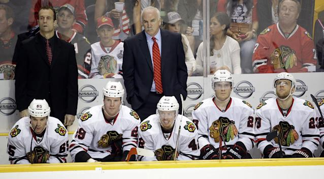 Chicago Blackhawks coach Joel Quenneville, center, and assistant coach Jamie Kompon, left, watch the action in the final seconds of an NHL hockey game against the Nashville Predators Saturday, April 12, 2014, in Nashville, Tenn. The Predators won 7-5. (AP Photo/Mark Humphrey)
