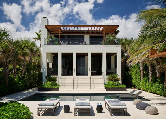 """<div class=""""caption""""> The back of Joyner's home was completely reconstructed by Wecselman and Kean. """"On the exterior, a theater-style stair leads you down to the pool deck from an exterior loggia. The procession of spaces from interior, covered loggia, covered trellis, beach, and vice versa is really what living in the subtropics is all about,"""" says Kean. Outside at the pool, the lounge chairs are by <a href=""""https://www.hollyhunt.com/"""" rel=""""nofollow noopener"""" target=""""_blank"""" data-ylk=""""slk:Holly Hunt"""" class=""""link rapid-noclick-resp"""">Holly Hunt</a> with tables by <a href=""""https://www.liaigre.com/en/"""" rel=""""nofollow noopener"""" target=""""_blank"""" data-ylk=""""slk:Liaigre"""" class=""""link rapid-noclick-resp"""">Liaigre</a> and poufs by <a href=""""http://www.paolalenti.it/en/"""" rel=""""nofollow noopener"""" target=""""_blank"""" data-ylk=""""slk:Paola Lenti"""" class=""""link rapid-noclick-resp"""">Paola Lenti</a>. </div>"""