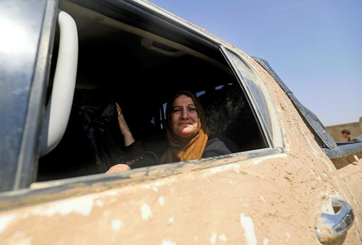 A member of an Armenian Christian family who fled Raqa smiles inside a car in Jazra, a western suburb of the northern Syrian city, on August 8, 2017 (AFP Photo/Delil souleiman)