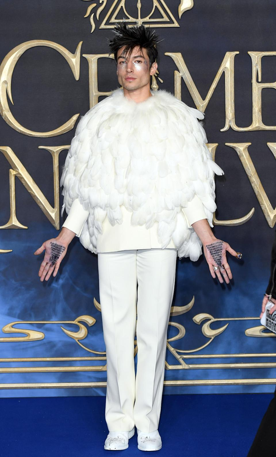 <p>Ezra Miller demonstrated his red carpet know-how in a white feathered cape and tailored trousers by Givenchy for a red carpet photocall. Silver hairtips and writing on his hands finished the unusual ensemble. <em>[Photo: Getty]</em> </p>